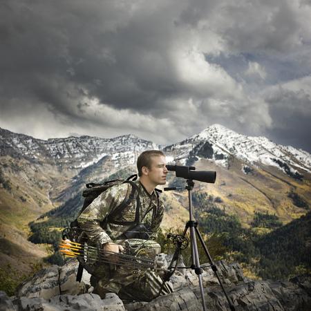 scouting: Hunter Using Binoculars To Spot Prey LANG_EVOIMAGES