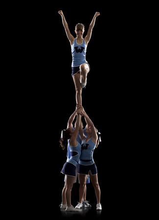 black cheerleader: Studio Shot Of Cheerleaders (16-17) Supporting Friend Standing On One Leg