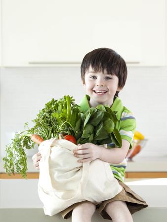 only boys: Usa,Utah,Portrait Of Smiling Boy (4-5) Holding Bag Of Vegetable