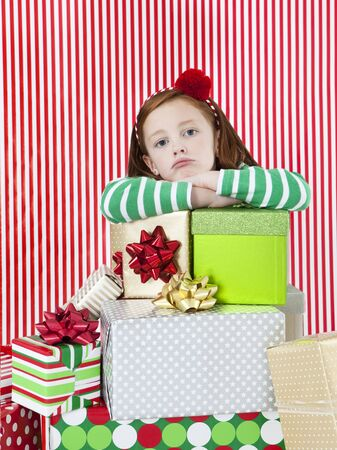 Studio Portrait Of Girl (4-5) With Stack Of Christmas Gifts