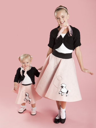 Portrait Of Girls (12-17 Months) And (10-11) In 1950S Style Costumes For Halloween