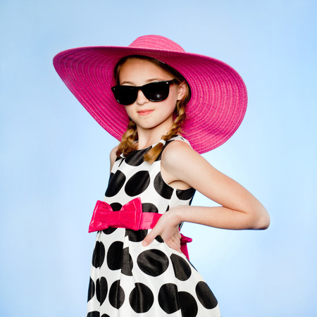 Studio Portrait Of Elegant Girl (10-11) Wearing Hat,Sunglasses And Dress
