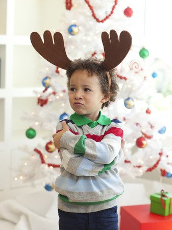 Happy Young Boy Deer Horns Standing  In Front Of Christmas Tree LANG_EVOIMAGES