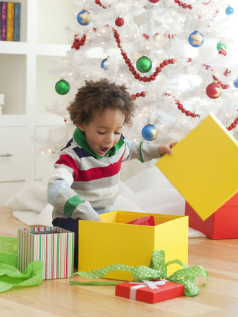 Young Boy Sitting Under Christmas Tree,Opening Christmas Presents