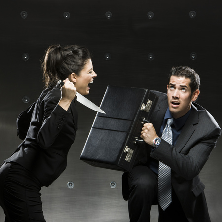Businesswoman Attacking Businessman With A Knife LANG_EVOIMAGES