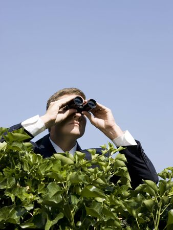 Man Looking Over A Hedge With Binoculars