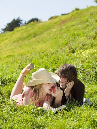 Usa,California,San Francisco,Young Couple Lying On Grass Eating Apple LANG_EVOIMAGES