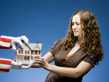 Person Holding A Miniature House While Uncle Sam Tries To Take It Away LANG_EVOIMAGES
