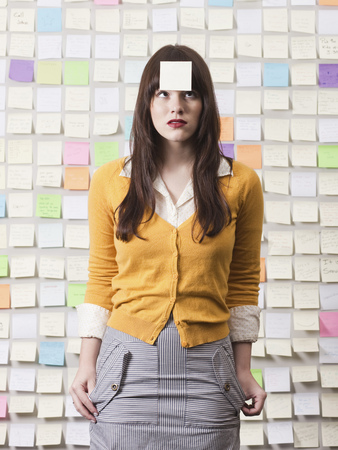 post it: Studio Shot Of Young Woman Looking At Post-It Note On Forehead