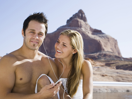 Young Couple At The Lake Listening To An Mp3 Player Together