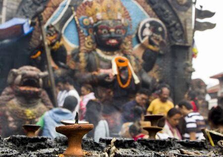 Very colorful and beautiful Hindu god image with some candles in the foreground at Durbar Square in Kathmandu, Nepal