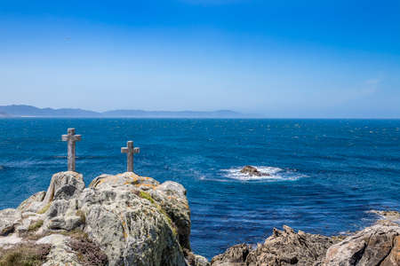 stone crosses on the coast gives death in the foreground and the brave Atlantic ocean in the background at the punta roncudo lighthouse. Lighthouse trail