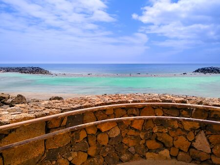 beach of jablillo in costa teguise lanzarote with its blue and green salty water of sea. View behind a wall of orange stone in a blue day of summer with some white clouds in the sky Фото со стока