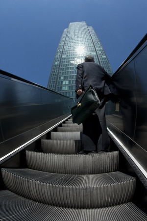 approaching: Man approaching business building from below going up with escalator Stock Photo