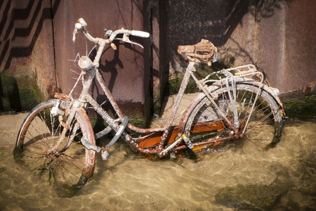 Drowned and vandalized rusty bicycle standing on river floor while ebb photo