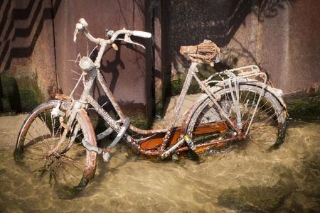 ebb: UtonÄ…Å' i zniszczone zardzewiaÅ'y rower stojÄ…cy na podÅ'odze rzeki podczas ebb Zdjęcie Seryjne