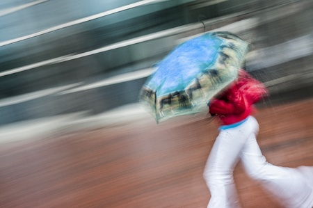 windy city: Female running from rain in red coat and white pants with blue umbrella