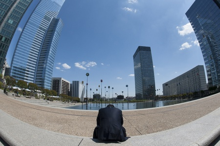 Man sitting tired and lonely in business district feeling broke and sad Stock Photo - 12954386