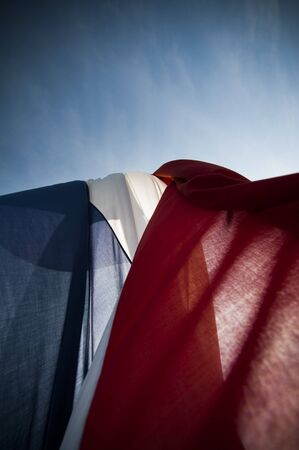 Dutch red-white-and-blue wrinkled flag against sun and blue sky in strong wind photo