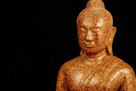 Buddha stone sculpture close-up black background macro