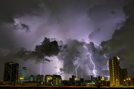 City landscape lightning storm behind clouds at night 版權商用圖片