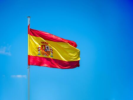 National Spanish flag in blue sky with clouds Spain