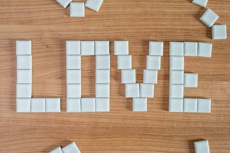 Love word with porcelain squares over wood background Stok Fotoğraf