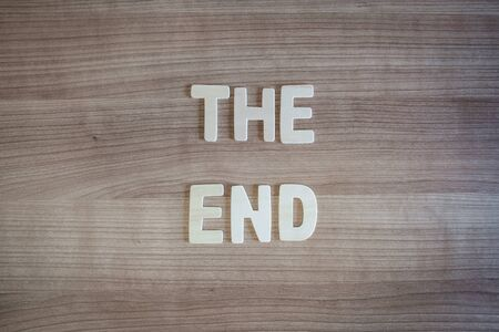 The End words with wood letters over wood background