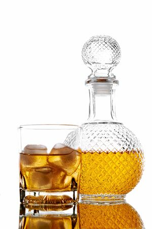 Bottle and glass with alcoholic drink with ice, on the rocks, whisky, rum, cognac, brandy, scottish, white background