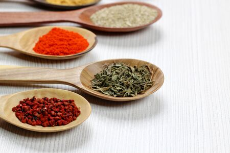 selective focus on Assortment of spices in wooden spoons, white background