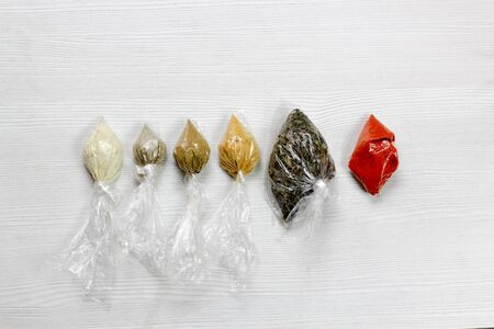 various spices and herbs packed in small transparent plastic bags on white background