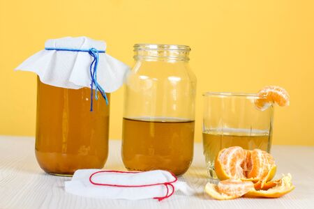 fermented drink, jun tea healthy natural probiotic in a glass jar, with a glass and tangerine ready to drink