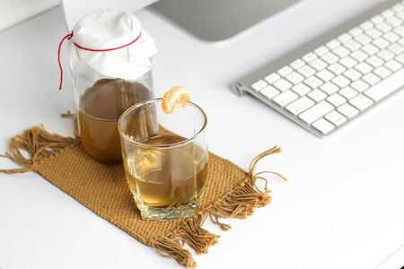 fermented drink, jun tea healthy natural probiotic in a glass jar, with a glass and tangerine ready to drink in the office Imagens