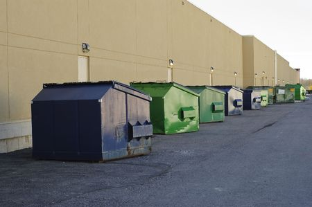 skip: Blue and green industrial garbage bins lined up outside along commercial building wall Stock Photo