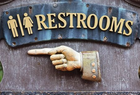 privy: Sign with hand pointing direction to male and female restrooms