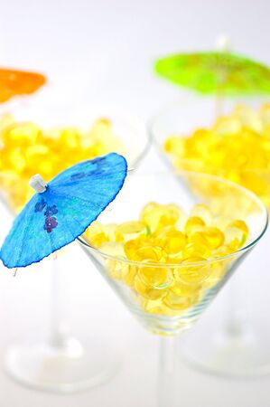 Three martini glasses filled with cod liver oil capsules, sources of vitamin a, vitamin d and omega-3, decorated with mini parasols, isolated on white photo