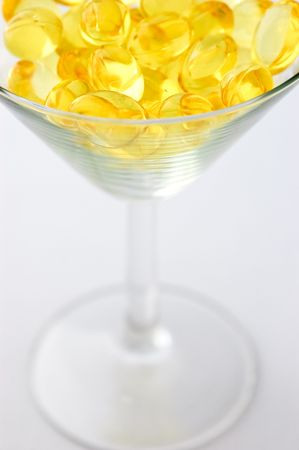 Macro of martini glass with yellow omega-3 pills photo