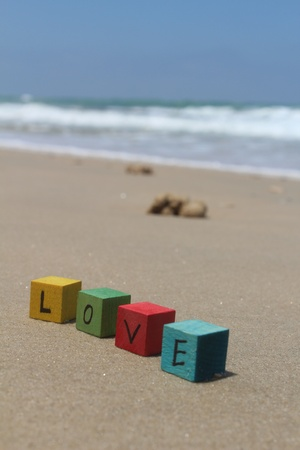 cherishing: The word LOVE written with wood cubes, at the beach Stock Photo