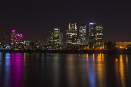 ondon: ONDON, UK - JUNE 06, 2015: Night view of Canary Wharf, a major business district located in London, UK. Its a home to the headquarters of numerous major banks and other professional service firms Editorial