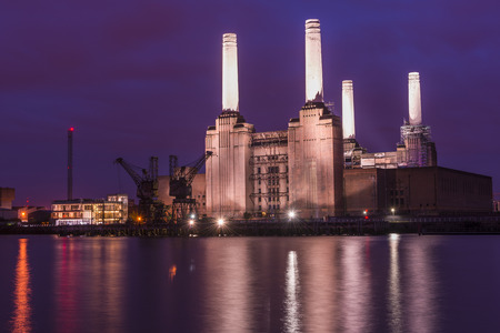 Night view of abandoned Battersea power station across river Thames, London, UK Фото со стока