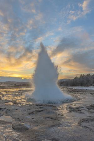 gush: Eruption of Strokkur Geyser against setting sun in Iceland Stock Photo