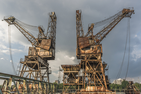decrepitude: Two rusty, derelict cranes at the abandoned Battersea power station, London, UK