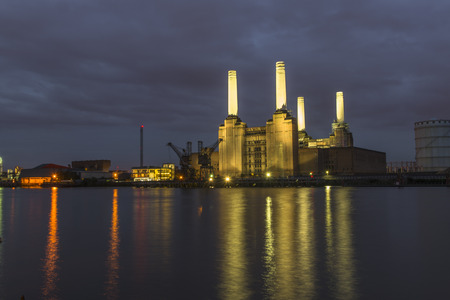old architecture: Night view of abandoned Battersea power station across river Thames, London, UK Stock Photo