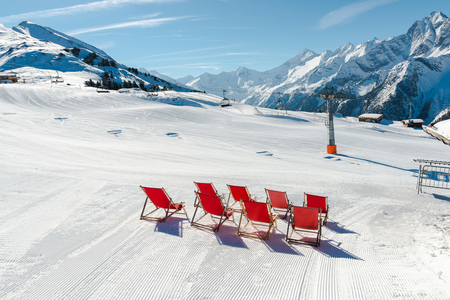 Empty red deck chairs on the snow in Mayrhofen ski resort, Austrian Alps