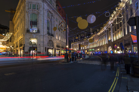 regent: LONDON - NOVEMBER 26th 2015: This years Regent Street Christmas lights feature shimmering golden sequins, cogs and coils which create a glittering setting for shoppers