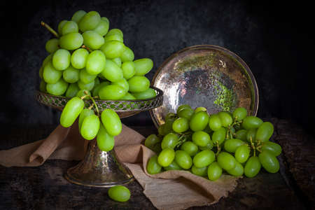 moody: Green grapes on dark background - vintage, moody style