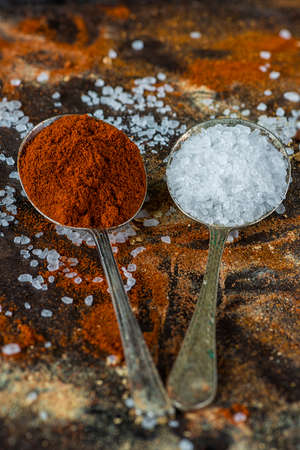 variability: Paprika and crystal salt on  rustic colorful background - closeup