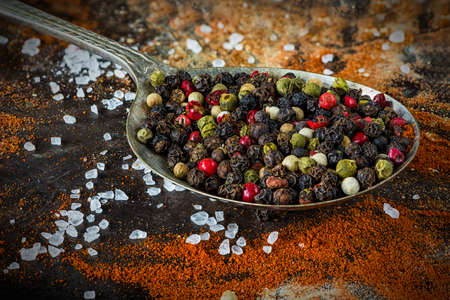 variability: A spoon with colorful peppercorns on rustic background - closeup