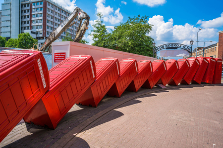 kingston: LONDON, UK - JULY 23, 2016: An art installation called Out of Order by David Mach in Kingston upon Thames. Its a series of 12 old red phoneboxes laid out as if they have fallen against each other.