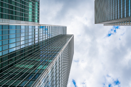 LONDON, UK - JULY 31, 2016: Upward view of a glass skyscraper in Canary Wharf - home to the headquarters of major banks, professional services firms, law, media and other businesses